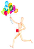 Wooden Dummy holding red heart and balloons. Wooden Dummy holding red heart with flying balloons Royalty Free Stock Photo