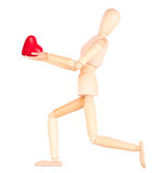 Wooden Dummy holding red heart. Isolated. Health insurance or love concept Royalty Free Stock Image