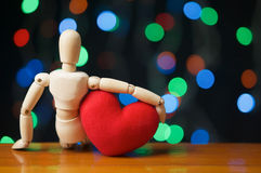 Wooden dummy hug red heart shape have bokeh as background Stock Images