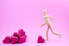 Wooden dummy are kicking paper box red heart shape to a pile of Stock Photo