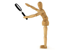Wooden dummy with magnifying glass Stock Image