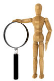 Wooden dummy with magnifying glass Stock Photos