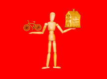 Wooden dummy man holding house and bike Royalty Free Stock Photos