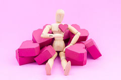 Wooden dummy and a pile of paper box red heart shape on pink bac Stock Photos