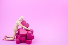 Wooden dummy and a pile of paper box red heart shape on pink bac Stock Image