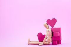 Wooden dummy and a pile of paper box red heart shape on pink bac Royalty Free Stock Photos