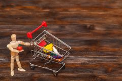 Wooden dummy puppet with mini shopping cart. Abstract food concept royalty free stock photography