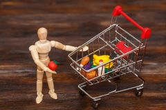 Wooden dummy puppet with mini shopping cart. Abstract food concept royalty free stock photo