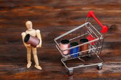 Wooden dummy puppet and mini shopping cart with thread spools royalty free stock photo