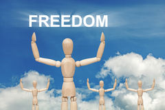Wooden dummy puppet on sky background with word FREEDOM. Abstract conceptual image stock images