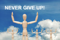 Wooden dummy puppet on sky with words NEVER GIVE UP Stock Photo