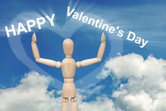 Wooden dummy puppet on sky with words VALENTINE`S DAY stock photos