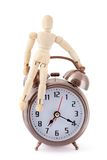Wooden dummy sitting on old-styled alarm clock. Stock Image