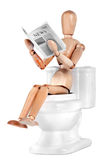 Wooden Dummy sitting on toilet Royalty Free Stock Image