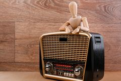 Wooden dummy stands in relaxed pose behind the radio receiver putting his hands on it. Wooden background. Wooden dummy stands in relaxed pose behind the radio Royalty Free Stock Photography