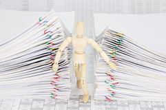 Wooden dummy try to escape from dual pile overload document. Of report with colorful paperclip on finance account Stock Photo