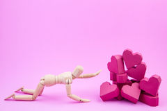 Wooden dummy was crawling to a pile of paper box red heart shape Royalty Free Stock Images