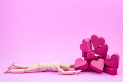Wooden dummy was crawling to a pile of paper box red heart shape Stock Image