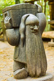 Wooden Dwarf. A wooden statue of a dwarf carrying a chest Stock Photography