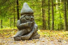 Wooden Dwarf. Wooden statue of a dwarf in the forest Royalty Free Stock Photo