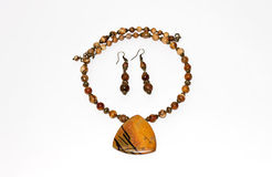 Wooden earrings and necklace with a brown stone. On a white background Stock Photography