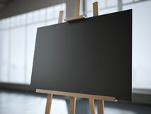 Wooden easel with a blank black canvas in modern interior. Royalty Free Stock Photography