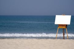 Wooden Easel and Blank Canvas on Beach. A blank canvas rests on a wooden easel on a beach Royalty Free Stock Image