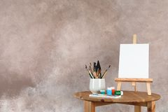 Wooden easel with blank canvas board and painting tools for children on table near color wall. Space for text royalty free illustration