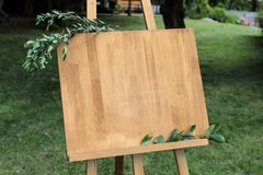 Wooden easel with a board. On the board written white paint - We. Lcome stock photos