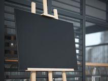 Wooden easel with a canvas on the street near cafe. Royalty Free Stock Image