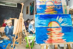 Wooden easel in the drawing class with drawings of children. foreground palette. Art class stock image