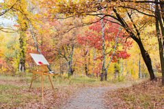 Wooden easel with empty canvas in autumn forest. Wooden easel with red oak leaf on the blank canvas near the walkway in autumn forest Royalty Free Stock Photos