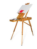 Wooden easel with empty canvas on a light background. Wooden easel tripod design with red oak leaf on the blank canvas and painting tool on a light background Stock Photo
