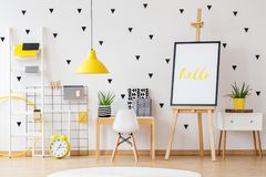 Wooden easel in kids room. Wooden easel in white and yellow kids playing room stock photo
