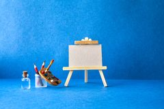 Wooden easel with textured blank paper canvas on blue background. Beautiful art class studio interior, watercolor. Brushes, pencils in a case, water. Artist`s stock photos
