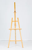 Wooden easel in white room Royalty Free Stock Images