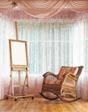 Wooden easel and wicker rocking chair composition Stock Photos
