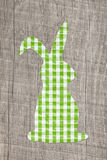 Wooden easter background with a green checked bunny. Royalty Free Stock Photography