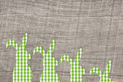 Wooden easter background with a green checked bunny family. Royalty Free Stock Photography
