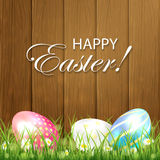 Wooden Easter background with three colorful eggs Royalty Free Stock Images