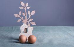 Wooden easter bunnies and chicken eggs. On table Royalty Free Stock Photos