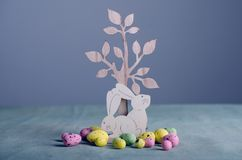 Wooden easter bunnies and chicken eggs. On table Stock Photography