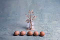 Wooden easter bunnies and chicken eggs. On table Stock Images