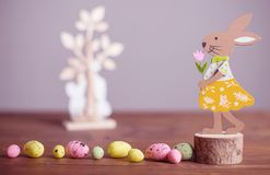 Wooden easter bunny and chicken eggs. Wooden easter bunny with flower and chicken eggs Royalty Free Stock Image