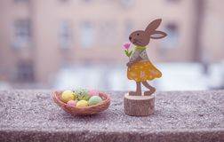 Wooden easter bunny and chicken eggs. Wooden easter bunny with flower and chicken eggs Royalty Free Stock Images