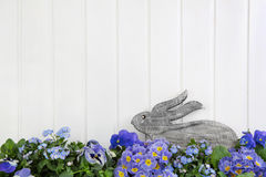 Wooden easter bunny sitting in blue and purple spring flowers. I. Easter bunny sitting in blue and purple spring flowers. Idea for a greeting card background in Royalty Free Stock Photo