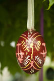 Wooden Easter egg. Hand-painted hanging on a tree Royalty Free Stock Photography