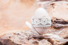 Wooden easter egg. Wood egg easter decoration crafting idea with lace Stock Image