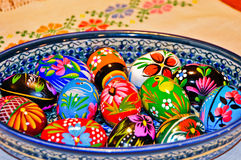 Wooden Easter eggs. Colorfully painted Polish wooden Easter eggs in a Polish ceramic bowl on a piece of hand woven cloth with cross-stitch Royalty Free Stock Photos