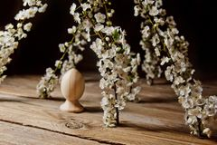 Wooden easter eggs among flowering cherry branches on a rustic table. symbolic composition of the spring holiday for a gift card. stock images